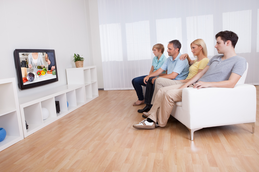 Family watching widescreen television